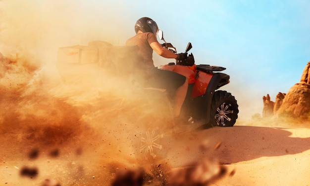 Atv in sella a una cava di sabbia, nuvole di polvere. pilota maschio in casco su quad, freeride estremo su quad tra le dune del deserto