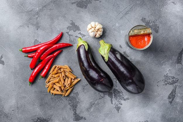 Ingredienti penne di melanzane pasta di melanzane, salsa di pomodoro al pepe, su sfondo grigio vista dall'alto.