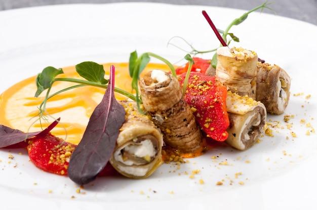 Rotoli di melanzane con formaggio su un piatto bianco la messa a fuoco selezionata cornice orizzontale
