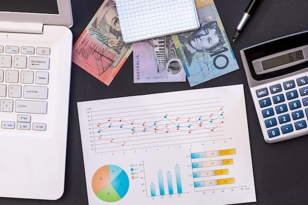 Computer portatile e diagramma del dollaro di aud su nero