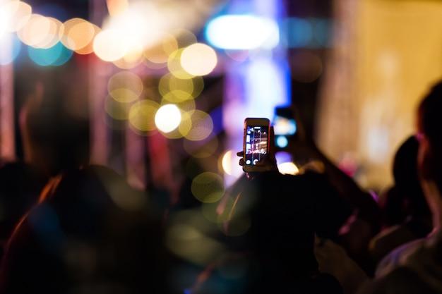 Pubblico scatta una foto sul cellulare in un festival di musica da concerto notturno gratuito