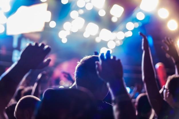Pubblico con le mani alzate in un festival musicale e luci che scendono da sopra il palco.