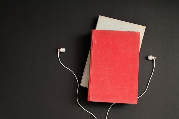 Concetto di audiolibro. cuffie e libro sulla tavola nera.