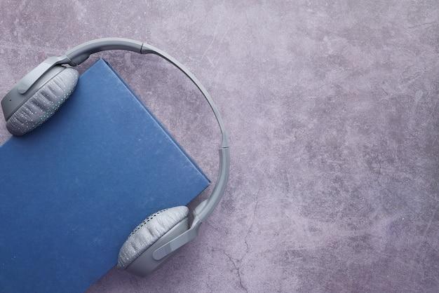 Concetto di audiolibro. cuffie e libro sul tavolo grigio.