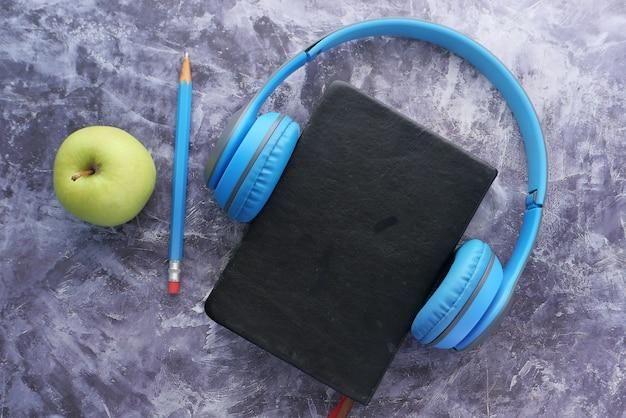 Concetto di audiolibro. cuffie e blocco note su sfondo nero.