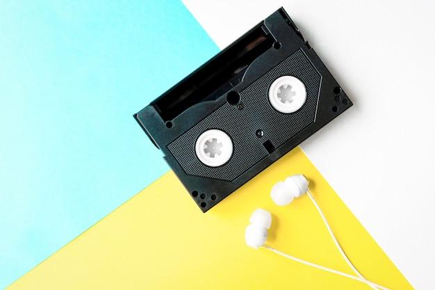Cassetta audio su uno sfondo colorato con apparecchiature per cuffie e oggetti di diversi periodi di tempo