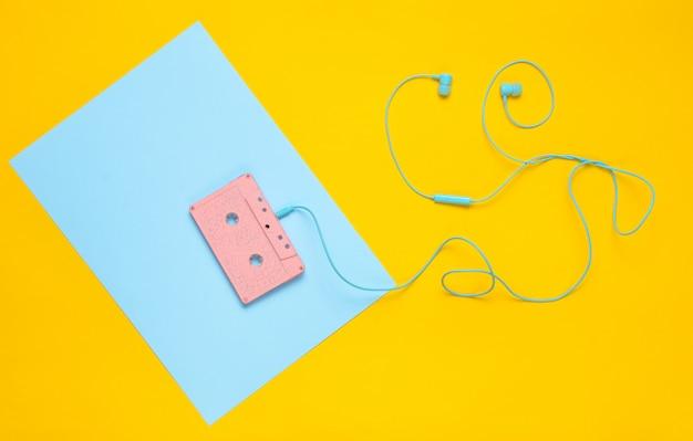 Audiocassetta e cuffie su uno sfondo giallo pastello blu. concetto musicale. stile retrò. minimalismo. vista dall'alto