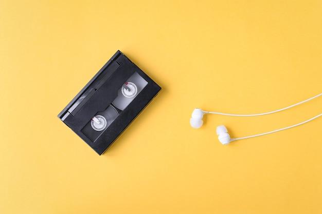 Cassetta audio e cuffie su sfondo giallo tempi nostalgici