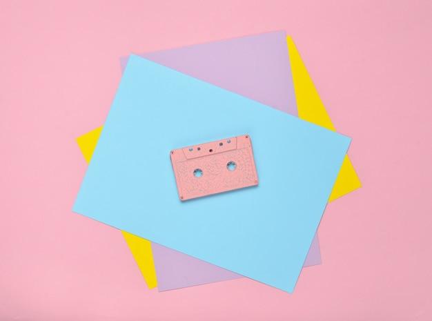 Cassetto audio su una parete di carta color pastello. tecnologia dei media retrò anni '80. musica, intrattenimento. vista dall'alto. tendenza minimalista