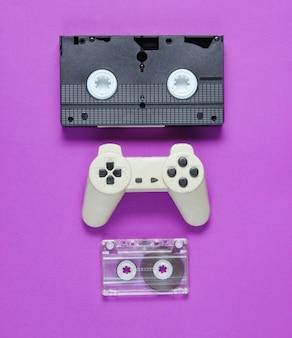 Audiocassetta, gamepad retrò, videocassetta su sfondo viola