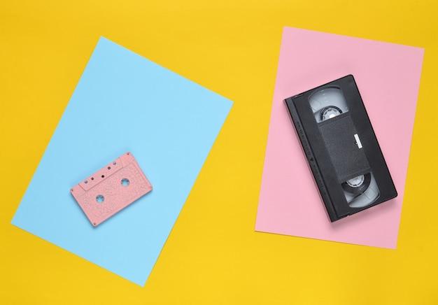 Audiocassetta e videocassetta su uno sfondo di carta colorata. vista dall'alto. minimalismo. copia spazio
