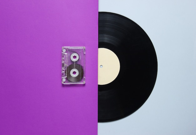 Audiocassetta, disco in vinile su un tavolo grigio viola. stile retrò. vista dall'alto