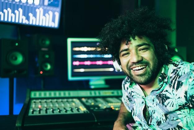Ingegnere audio che registra nuova musica lavorando all'interno dello studio di produzione - focus on face