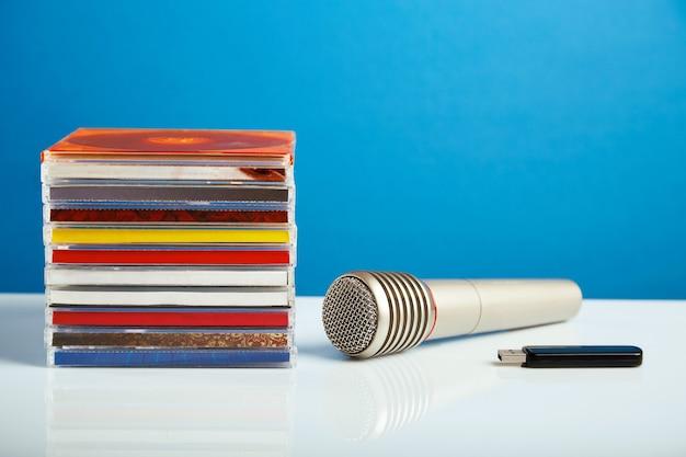 Microfono audio con cd e un'unità flash su un tavolo di legno.