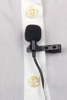 Registrazione audio del suono su un microfono a condensatore. il microfono lavalier è fissato con una clip sul primo piano di una camicia da donna