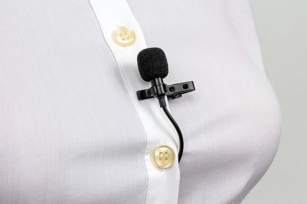 Registrazione audio del suono su un microfono a condensatore. il microfono lavalier è fissato con una clip sul primo piano della camicia di una donna.