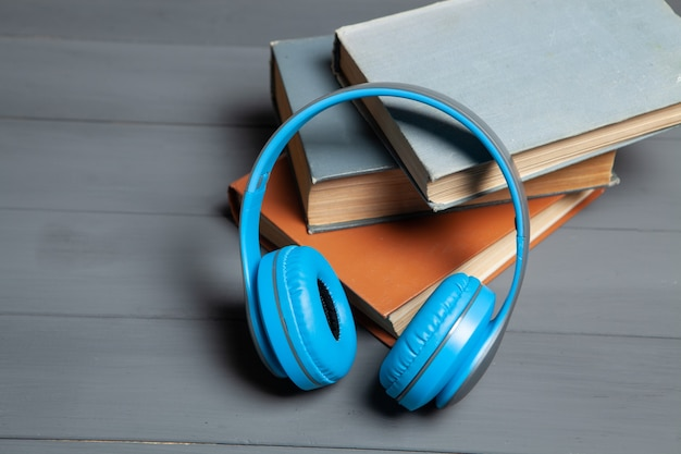 Concetto di audiolibro. libri e cuffie sul tavolo in legno