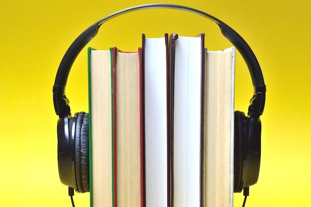 Concetto di audiolibro. una pila di libri con le cuffie. avvicinamento