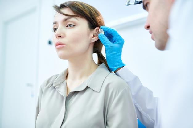 Audiologo examining woman