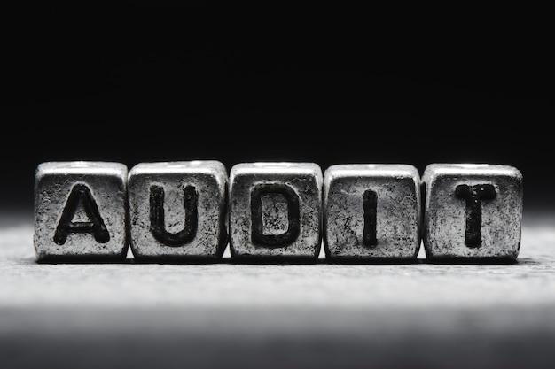 Concetto di audit. iscrizione 3d su cubi di metallo su sfondo nero grigio isolato