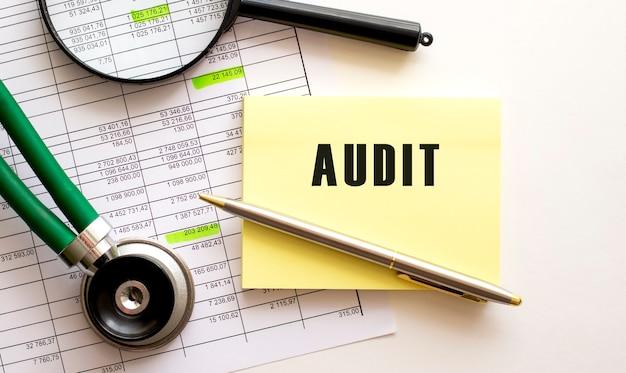 Testo audit su un adesivo sul desktop penna e lente d'ingrandimento