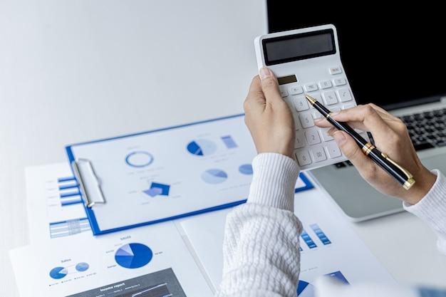 Il revisore sta premendo la calcolatrice bianca, è il revisore dei conti dell'azienda ed è responsabile del controllo dell'accuratezza di tutti i documenti relativi a entrate e uscite dell'azienda. concetto di revisione contabile.