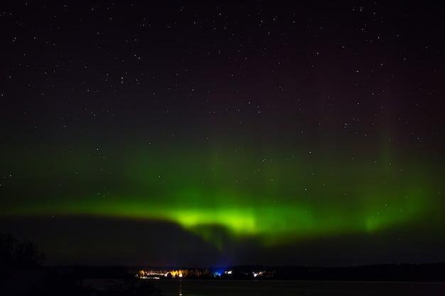 Aurora boreale sopra la città sulla costa. luci polari nel cielo stellato notturno sul lago.