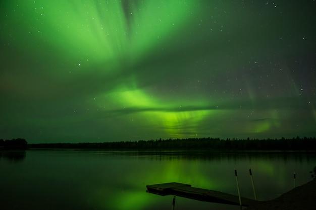 Aurora boreale sopra il lago in finlandia, idilliaco scenario notturno