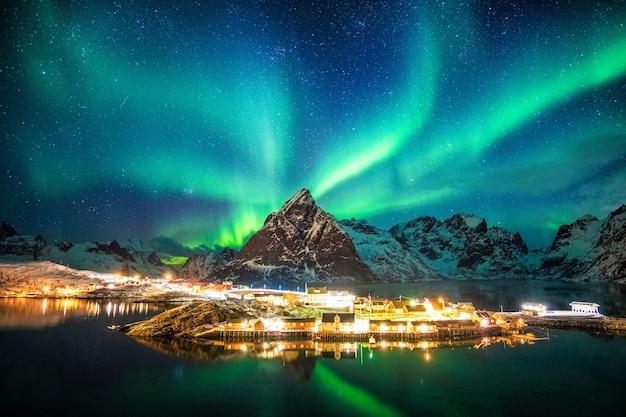 Aurora boreale sulle montagne nel villaggio di pescatori di sakrisoy, lofoten, norvegia