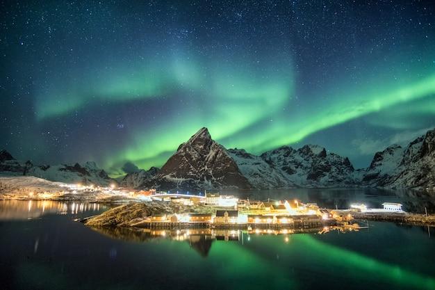 Aurora boreale sulle montagne nel villaggio scandinavo che brilla a sakrisoy, lofoten, norvegia