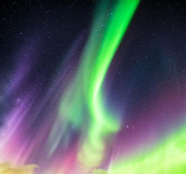 Aurora boreale o aurora boreale verde e viola con stelle nel cielo notturno sul circolo polare artico