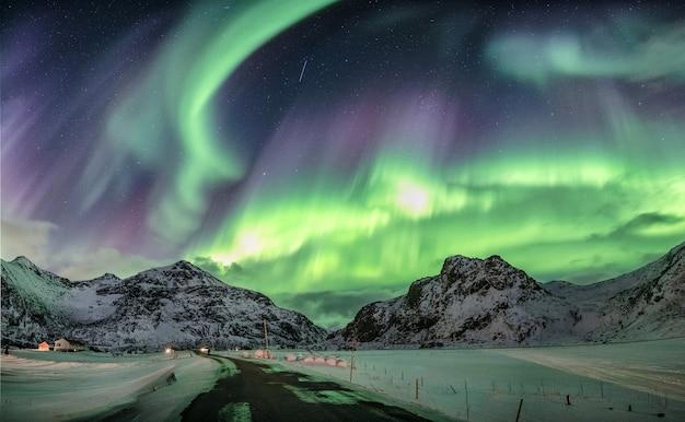 Aurora boreale, luci del nord sulla catena montuosa della neve a flakstad, isole lofoten, norvegia,