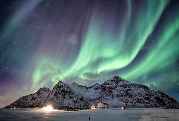 Aurora boreale con stellato sopra la catena montuosa della neve con illuminazione casa a flakstad, isole lofoten