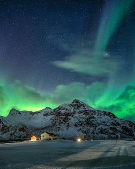 Aurora boreale con stellato sulla montagna innevata e villaggio nordico di notte a flakstad, isole lofoten, norvegia