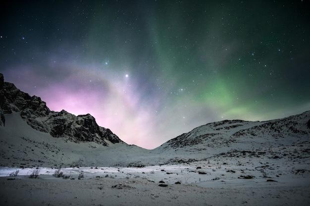 Aurora boreale con l'alba che splende sulla catena montuosa nel cielo notturno in inverno
