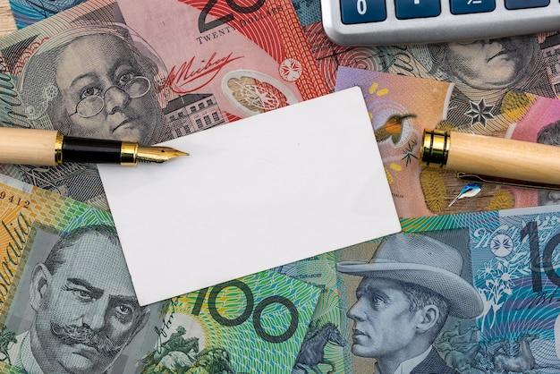Dollaro australiano con biglietto da visita, penna e calcolatrice