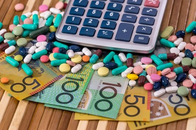 Dollari australiani con pillole colorate e calcolatrice