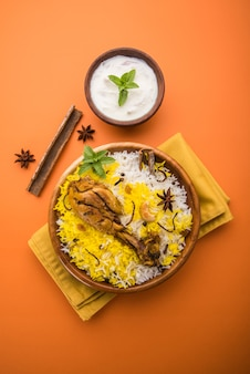 Autentico pollo biryani servito in una ciotola o in un piatto su sfondo colorato o in legno. è una deliziosa ricetta di riso basmati mescolato con pollo marinato piccante servito con insalata. messa a fuoco selettiva