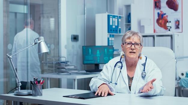 Autentica dottoressa anziana esperta che parla con la telecamera e fornisce consulenza medica online da una clinica moderna privata. servizio sanitario a distanza durante la pandemia globale di covid 19. la medicina guarisce