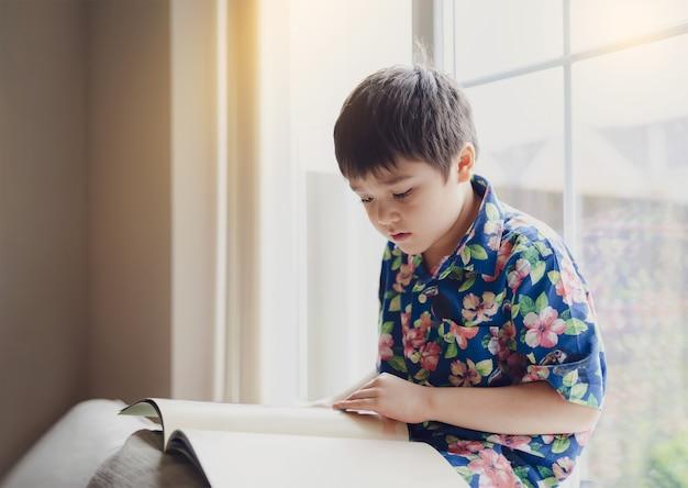 Autentico bambino che legge un libro al mattino