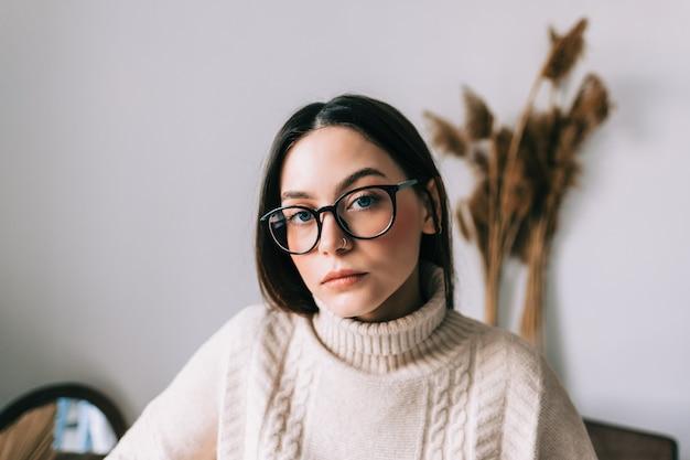 Ritratto di stile di vita autentico di pensierosa giovane donna caucasica in occhiali a casa