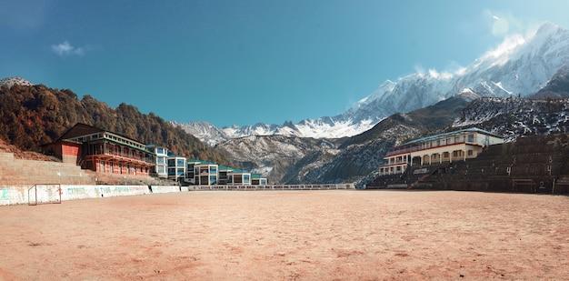 Un'autentica arena di calcio sabbiosa circondata dalle montagne innevate del nepal foto tonica