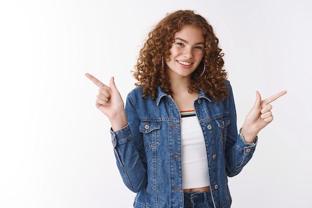 Autentico studio shot attraente sfacciata giovane ragazza rossa lentiggini cicatrici post-acne sorridente sfacciato divertirsi divertirsi promuovendo punto lati diversi sinistra destra mostra fantastici prodotti varianti