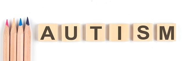 Concetto di autismo - blocchi di legno alfabeto su sfondo bianco con matite