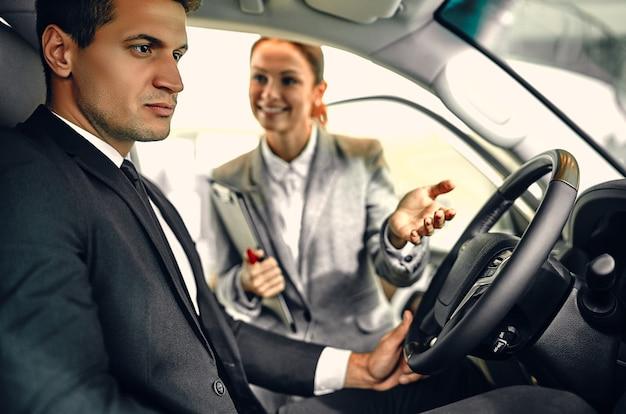Affari automobilistici, vendita di auto, consumismo e concetto di persone - uomo d'affari con concessionario di auto in auto show o salone.
