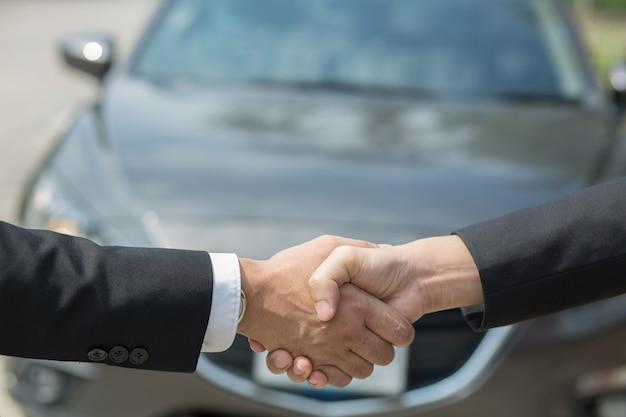 Affari automobilistici. primo piano di un commerciante di uomo d'affari offre auto al nuovo proprietario e stretta di mano tra due congratulazioni ai clienti. filtro tono all'aperto soleggiato al mattino.