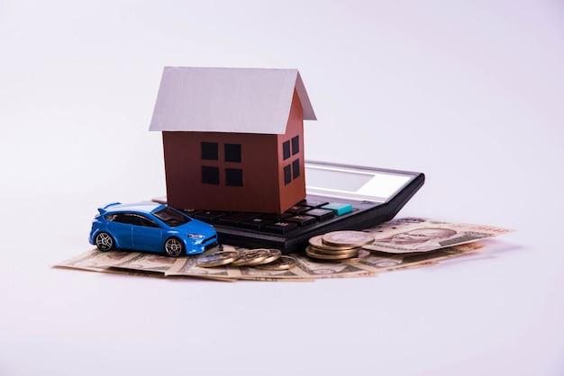 Finanziamento automatico e prestito abitativo o acquisto in india - concetto che mostra il modello 3d di auto e casa, chiavi, banconote e calcolatrice in valuta indiana ecc.