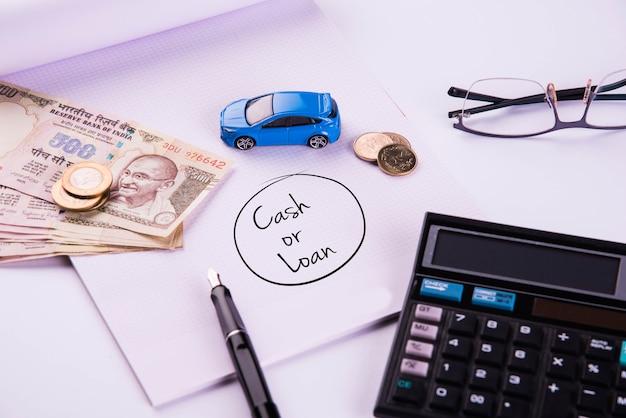 Finanziamento automatico o prestito in india - concetto che mostra il modello di auto giocattolo, chiavi, banconote in valuta indiana e calcolatrice per calcoli emi ecc. disposti su sfondo chiaro
