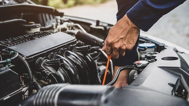 Il meccanico auto sta controllando il livello dell'olio motore dell'auto del veicolo