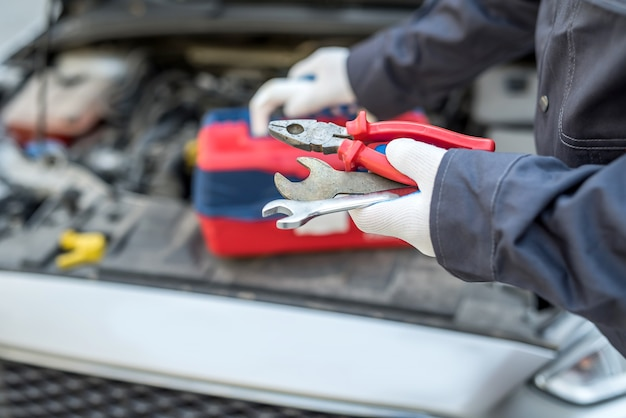 Meccanico auto in riparazione auto tenendo la chiave della chiave e strumenti. diagnostica automobilistica